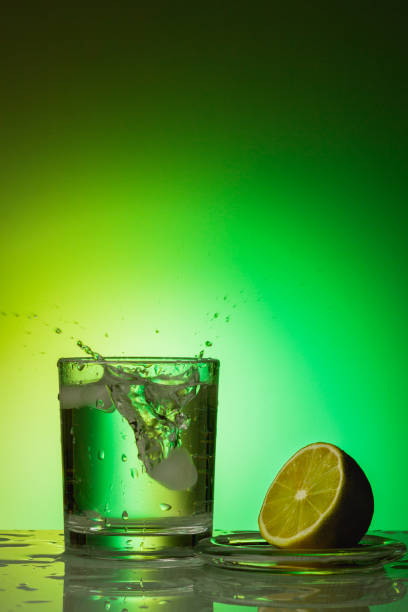 Splashes in a glass of water on a colored background stock photo