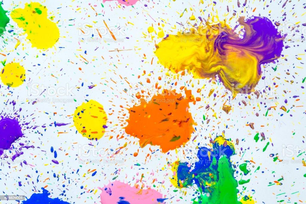 Éclaboussures de peinture aquarelle multicolore tombe sur un fond blanc. photo libre de droits