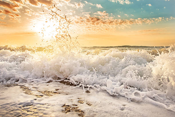 splashes of wave at sunrise. - wave pattern stock photos and pictures