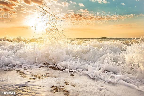 Photo of Splashes of wave at sunrise.