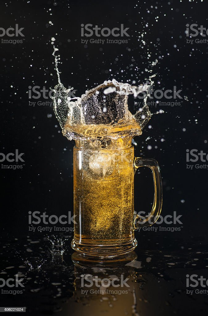 Splashing beer with ice cube stock photo