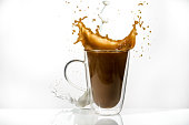 High-speed photo of coffee splashing out of a glass coffee cup with milk falling with white background