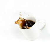 A tilted cup of coffee with splashing coffee pouring out on to a white background.