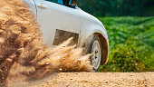 splashing dust and  gravel from rally race car