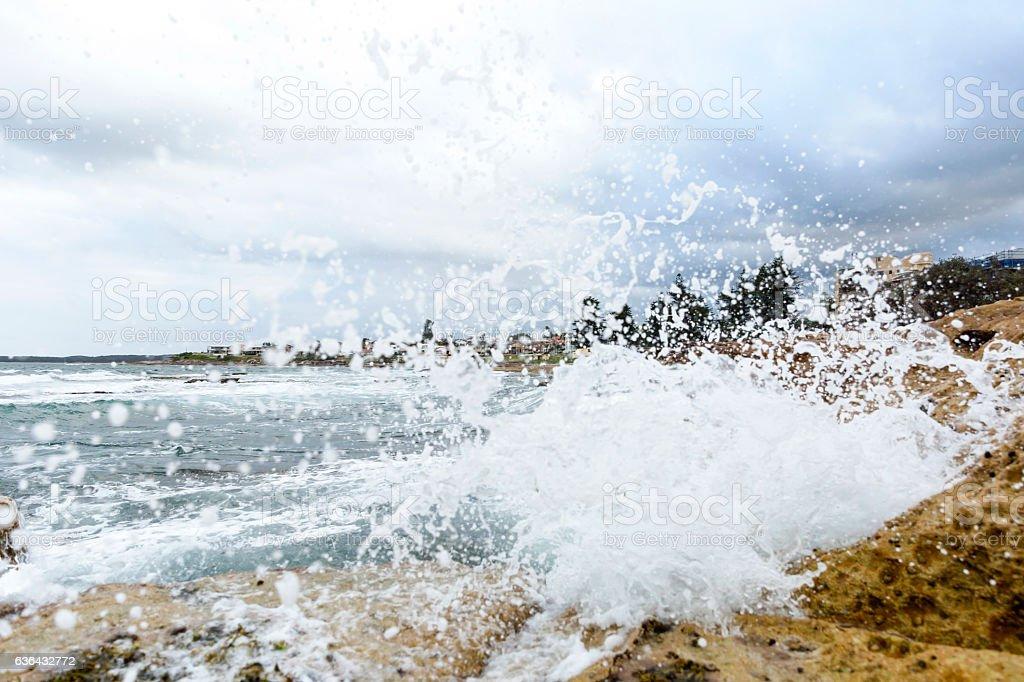 Splashing ocean water over the rocks, coastline in background stock photo
