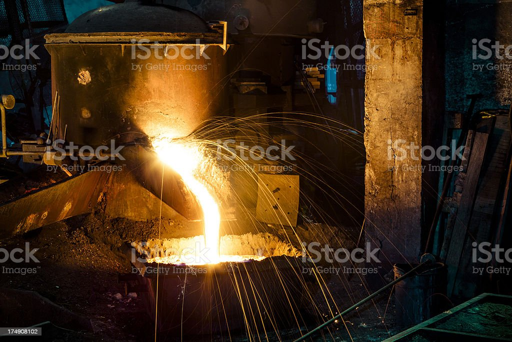 Splashing of iron water and motion unrecognizable  workers royalty-free stock photo