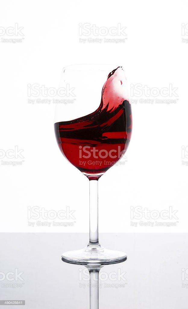 Splashing red wine in a glass stock photo
