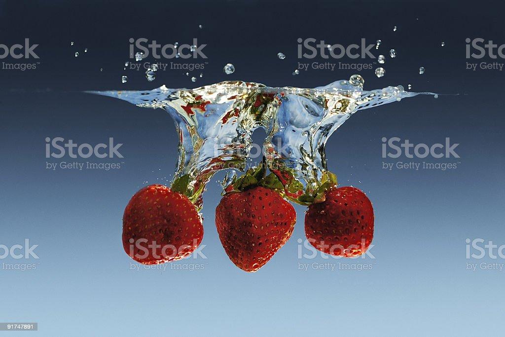 Splashing strawberries stock photo
