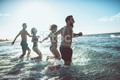 Happy People Splashing Through The Waves While Holding Hands