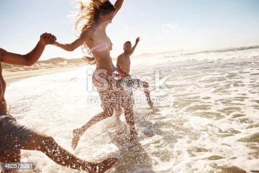 Two young couples running through the water at the beach