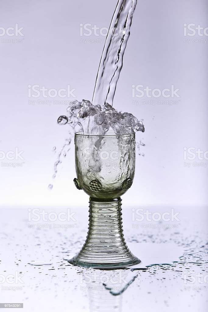 Splashing water into an old wine glass royalty-free stock photo