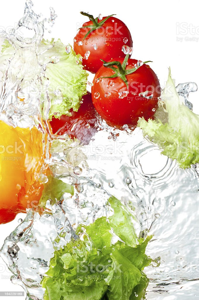 Splashing water with tomatoes, pepper and lettuce royalty-free stock photo