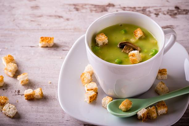 Split pea soup in white cup on white board stock photo