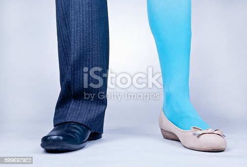 Front view of one male and one female leg as if belonging to one person. Transsexualism concept