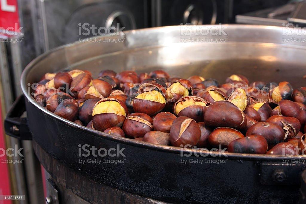 Split roasted chestnuts in metal pan in street cafe royalty-free stock photo