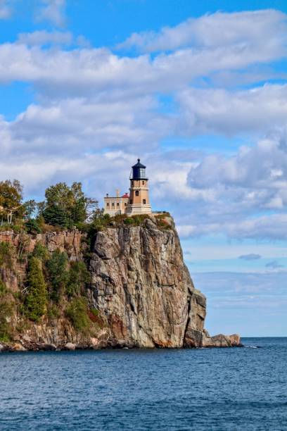 Split Rock Lighthouse on Lake Superior with blue sky and white clouds stock photo