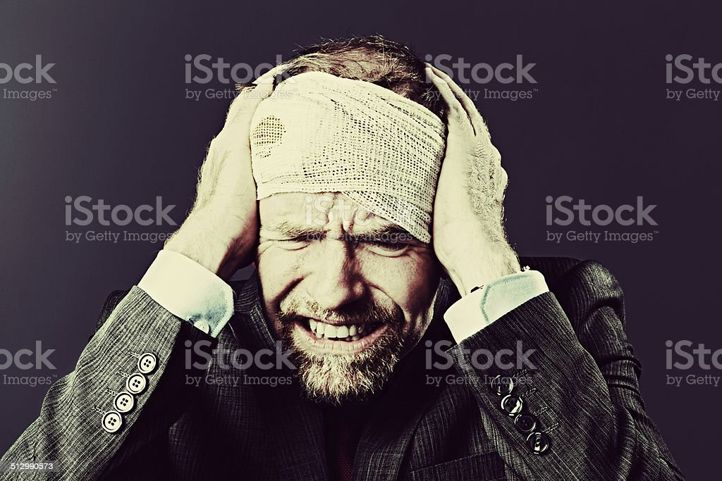 A mature businessman with his head wrapped in bloodstained bandages...