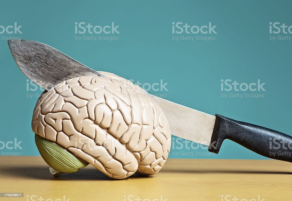 Splitting headache! Large knife chops into model brain royalty-free stock photo