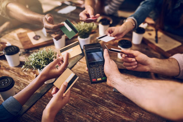 Splitting it six ways High angle shot of a group of friends offering their bank cards to pay the bill at a cafe playing card stock pictures, royalty-free photos & images