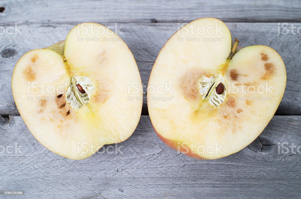 Spoiled apple cut in two half on wooden background stock photo