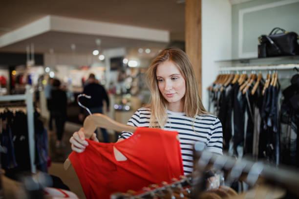 zichzelf te verwennen met nieuwe cothes - kledingwinkel stockfoto's en -beelden