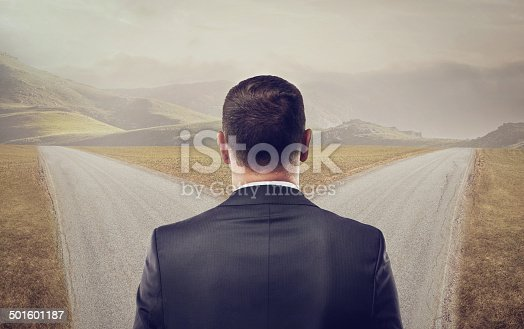 Rearview shot of a well-dressed man standing at a crossroads - ALL design on this image is created from scratch by Yuri Arcurs'  team of professionals for this particular photo shoothttp://195.154.178.81/DATA/i_collage/pi/shoots/783652.jpg