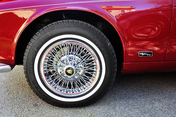 Spoked wheel of a Jaguar XJ Ales, France - April 11, 2015: Spoked wheel of a Jaguar XJ photographed gathering of old cars Town Hall Square in the town of Ales, in the Gard department  jaguar xj stock pictures, royalty-free photos & images