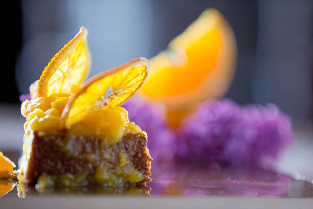 sponge cake garnished with clices of dried orange - food styling stock photos and pictures