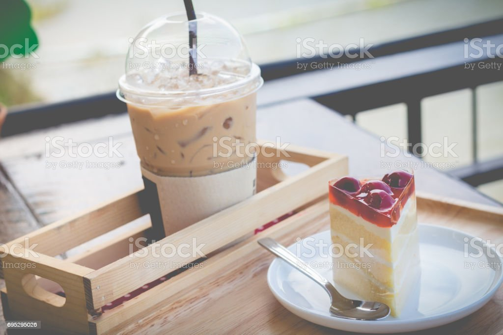 Sponge cake with cherry syrup. Peace of cherry cake serve with iced coffee in cozy outdoor cafe. stock photo
