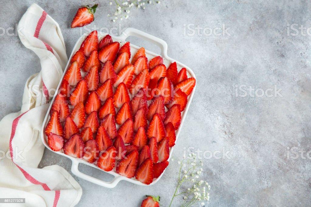 sponge  cake with cream cheese and fresh strawberry on white baking dish stock photo