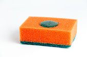 Sponge for washing dishes on a white background with a drop of detergent.