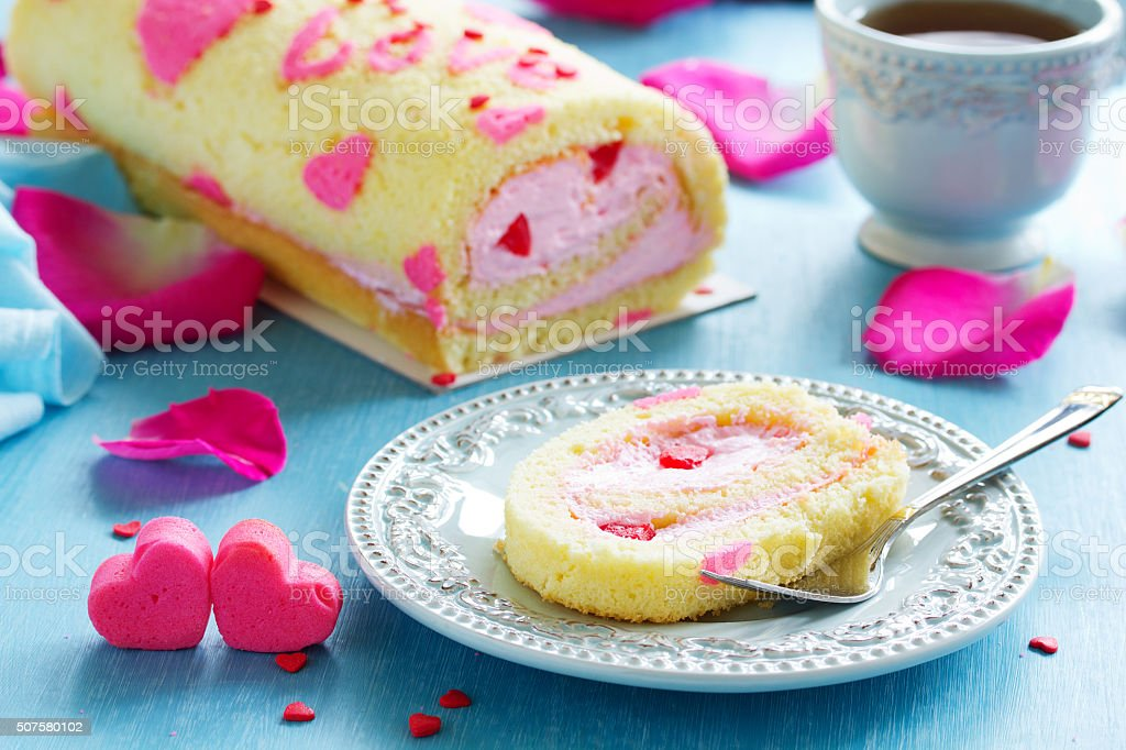 Sponge roll with cream rose on Valentine's Day. stock photo