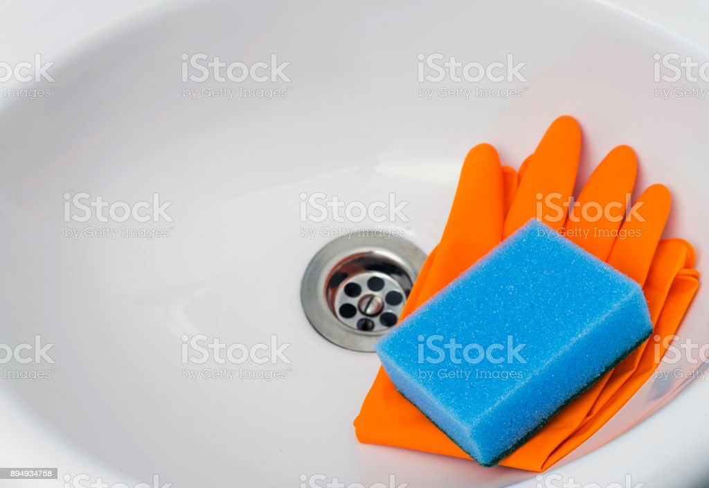 Sponge with orange rubber gloves in the sink. Cleaning service.