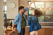 Shot of a happy young couple dancing together at home
