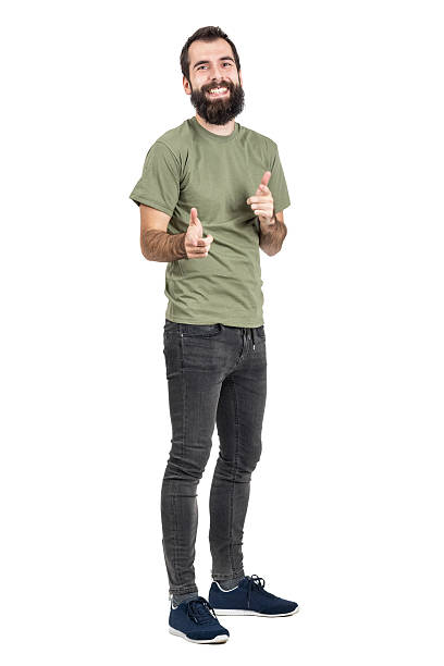Spontaneously laughing man in green t-shirt pointing fingers at camera Spontaneously laughing bearded man in green t-shirt pointing fingers at camera. Full body length portrait isolated over white studio background men in tight jeans stock pictures, royalty-free photos & images
