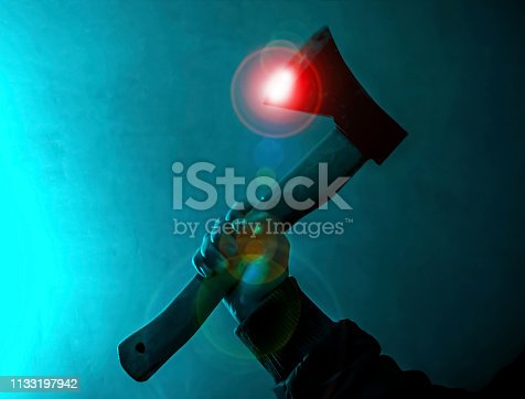 ax held in the darkness with glow and reflections on blue color background