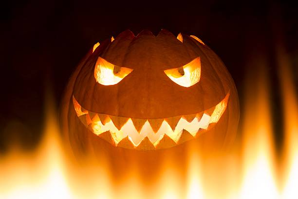 spooky carved halloween pumpkin in hot burning hell fire flames - demoniac stock pictures, royalty-free photos & images