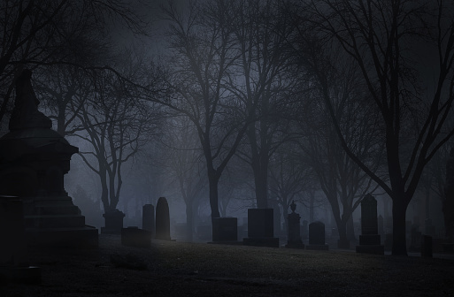 Spooky cemetery at night with fog. Desaturated color.
