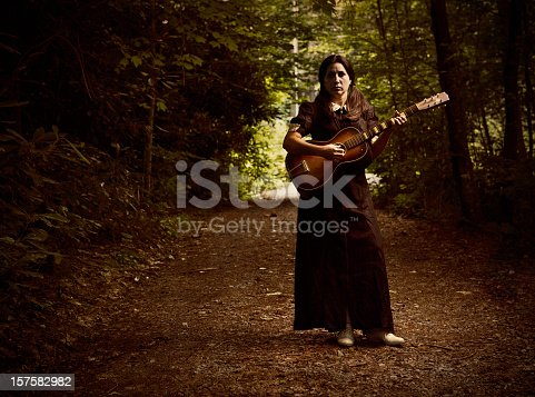 woman wearing a victorian style black dress, standing in the forest with an old acoustic guitar, some creepy music anyone?