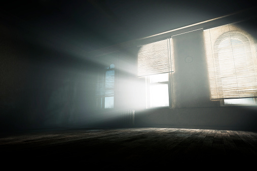 Spooky empty room with mysterious light beams