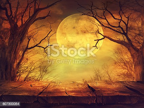 istock Spooky forest with full moon and wooden table 607300054
