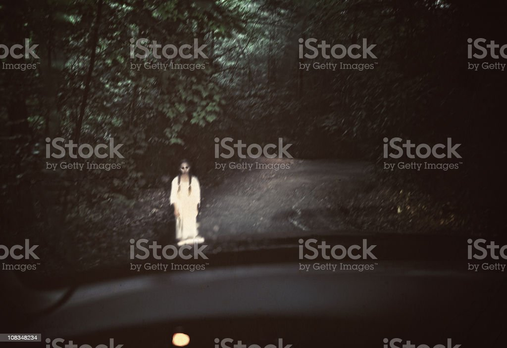 Spooky ghost in white standing in the middle of a dark road stock photo