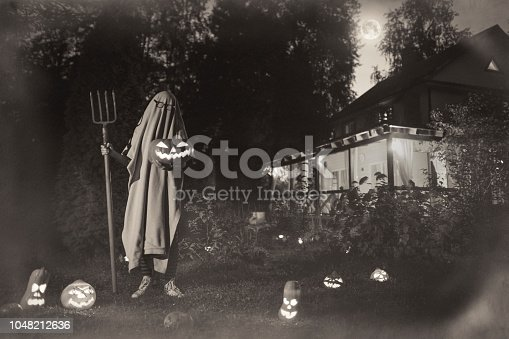 Child dressed as ghost standing near house in autumn at Halloween