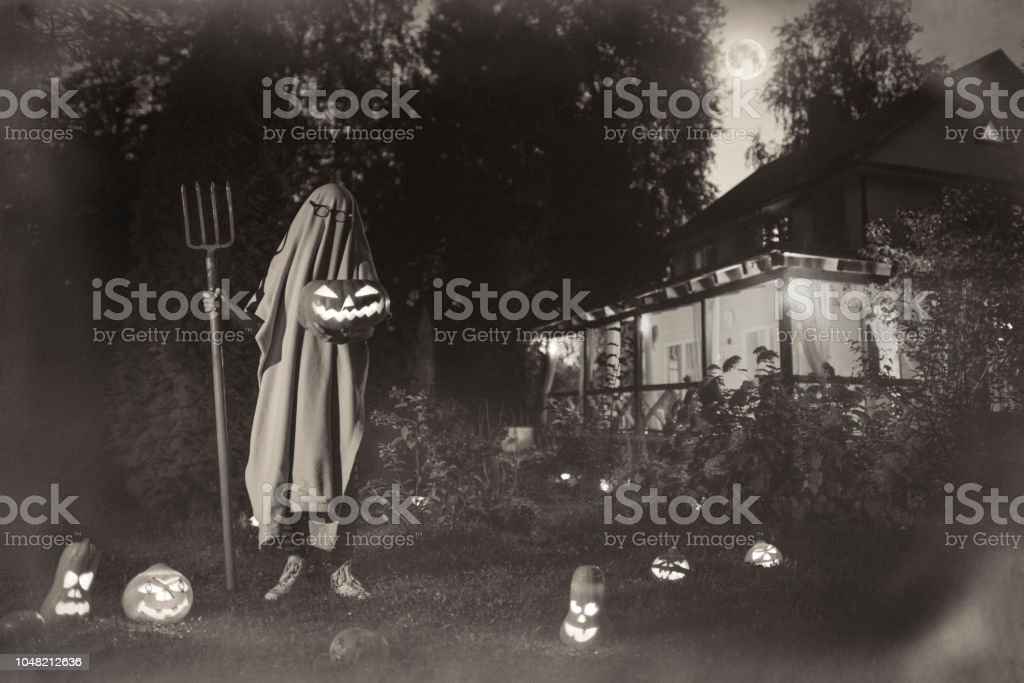 Spooky ghost near haunted house at Halloween in vintage style stock photo
