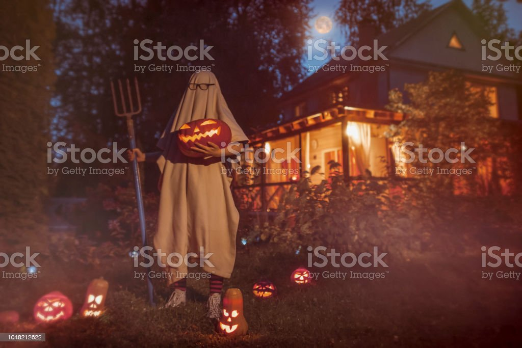 Spooky ghost near haunted house at Halloween stock photo