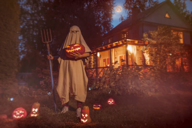 gruselige geist in der nähe von geisterhaus an halloween - geist kostüm stock-fotos und bilder