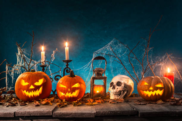 Spooky Halloween background Spooky Halloween pumpkins on wooden planks with spooky background. carving knife stock pictures, royalty-free photos & images