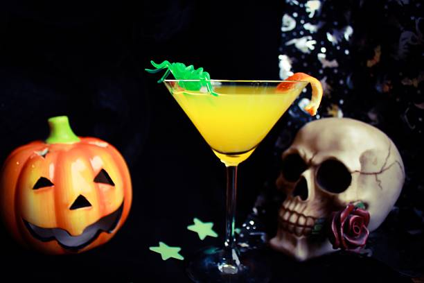 Spooky Halloween Drink Orange halloween drink with a carved pumpkin and skull ornaments deathly stock pictures, royalty-free photos & images