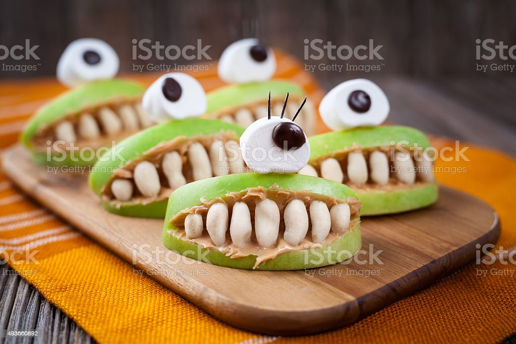 Spooky halloween edible apple monsters healthy natural dessert. Horror party stock photo