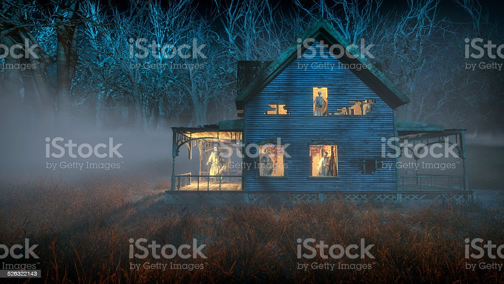Spooky halloween house with ghosts standing in the windows. stock photo